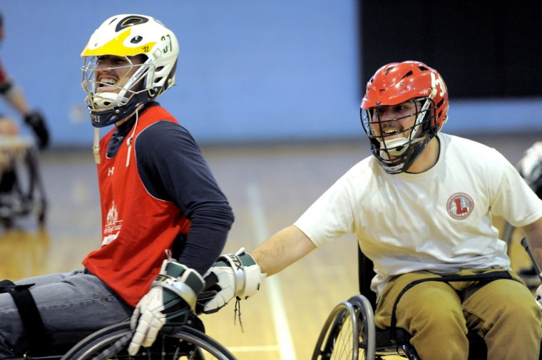 Left to right, Josh Burford, tries to pull away as his brother, Tyler Burford, holds onto his wheelchair. Both men, from Glenwood, VA, are able-bodied and are attending a Wheelchair Lacrosse Clinic in support of (not pictured) Ryan Beale, 24, Suffolk, VA. Tyler and Beale were on the Lynchburg lacrosse team together. (Kim Hairston/Baltimore Sun)
