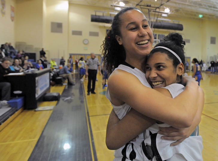 Patterson Mill guard Qalea Ismail (left) gets a congratulatory embrace from teammate Sia Barnes after Ismail - daughter of Baltimore Ravens retired player Qadry Ismail - drained her 1,000th point on a free throw against the Aberdeen Eagles. (Karl Merton Ferron/Baltimore Sun)
