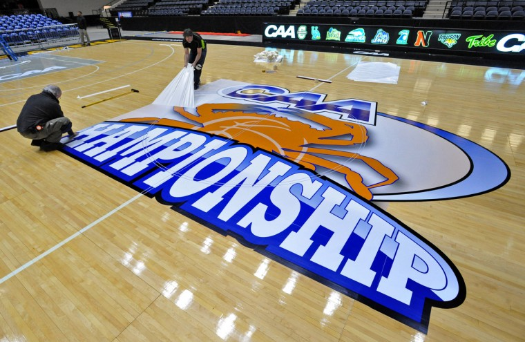 Dick Hageman, left, and Jeff Knab, right, of Art At Work, install the CAA logo and other decals on the basketball court of the Baltimore Arena. The CAA basketball tournament was held in Baltimore for the first time. (Amy Davis / Baltimore Sun)