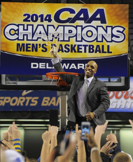 Delaware basketball coach Monte' Ross holds up the net after the winning the CAA tournament. (Lloyd Fox/Baltimore Sun)