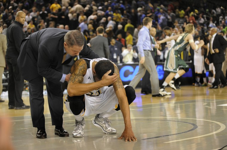 Towson Tigers head coach Pat Skerry comforts player Mike Burwell, after their team lost to William & Mary in the CAA men's basketball game at the Baltimore Arena. (Algerina Perna/Baltimore Sun)