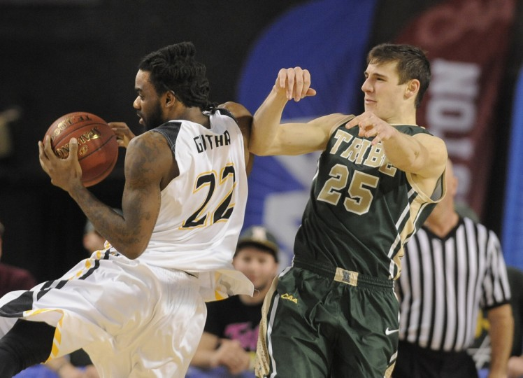 In the second period, Towson Tigers player Rafriel Guthrie #22, left, grabs the ball in William & Mary's court. At right is player Terry Tarpey #25. (Algerina Perna/Baltimore Sun)