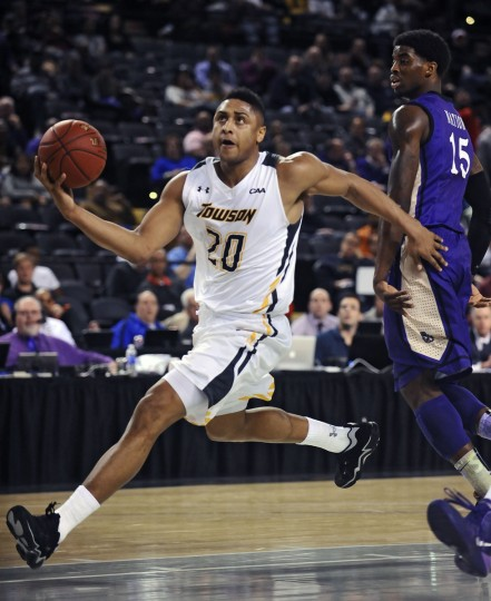 Towson's Jerrelle Benimon, left, drives toward the basket past James Madison's Andre Nation (315), right, in the first half. (Kenneth K. Lam/Baltimore Sun)