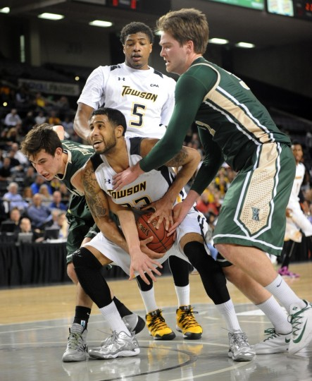n the first period, Towson Tigers player Mike Burwell, #23 in center, manages to keep the ball as he's challenged by William and Mary players Omar Prewitt #4, left, and Sean Sheldon #31 right. (Algerina Perna/Baltimore Sun)