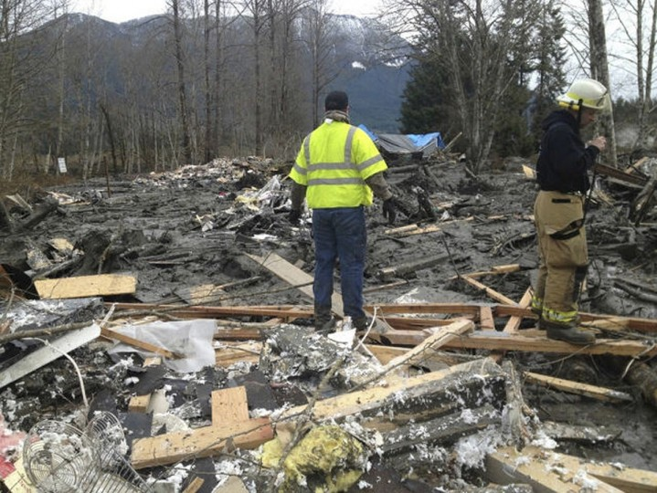 Officials survey a large mudslide in this handout photo provided by the Washington State Police near Oso, Washington, March 22, 2014. The mudslide pushed debris and at least one house onto Highway 530 near Oso Saturday morning, according to local news reports. Search and rescue crews were responding to the scene. (Washington State Police/Handout via Reuters)