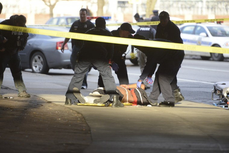 A victim of a shooting lies on the ground along Centre Street under I-83 awaiting medical attention. (Christopher T. Assaf/Baltimore Sun)