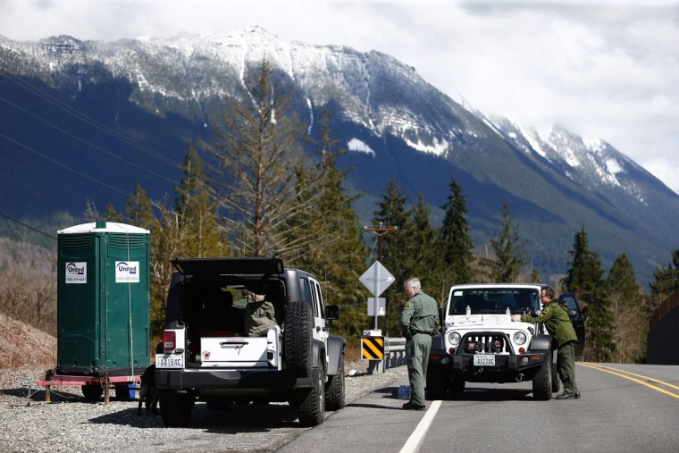 Snohomish County Sheriff officers monitor the scene a short ways up the road from the mudslide at mile 37 on Highway 530 on Sunday, March 23, 2014, the day after a giant landslide occurred near Oso, Washington. (Lindsey Wasson/Seattle Times/MCT)