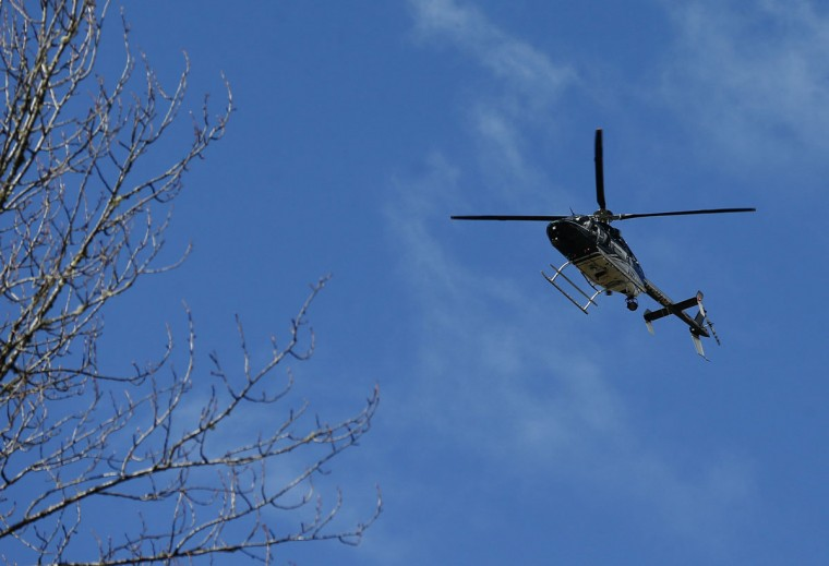 A Snohomish County Sheriff helicopter flies over the scene on Highway 530 next to mile marker 37 on Sunday, March 23, 2014, the day after a giant landslide occurred near mile marker 37 near Oso, Washington. (Lindsey Wasson/Seattle Times/MCT Photo)