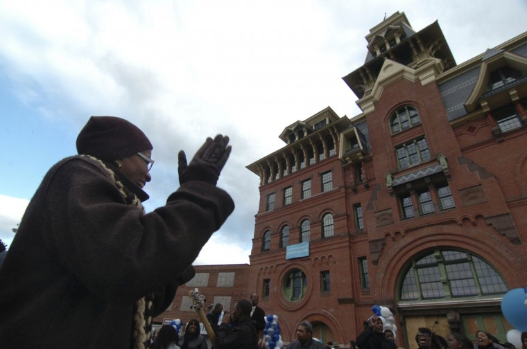 Bernadette Taylor, a Southern Baptist church member who lives in E. Baltimore, claps to the music of her church choir, Southern Baptist church, who performed at a renovation celebration in front of American Brewery. (Algerina Perna/Baltimore Sun)