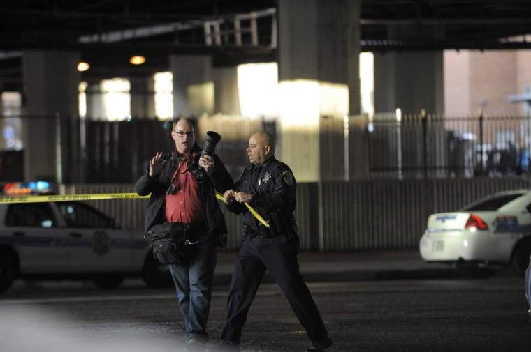 Baltimore Sun photographer Christopher T. Assaf is confronted by police at the scene of a shooting along Centre Street under I-83. (Lloyd Fox/Baltimore Sun staff)