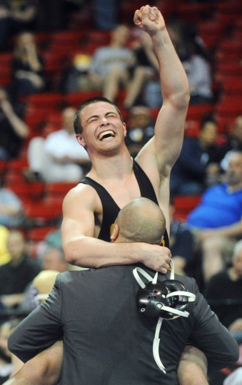 South Carroll's Jake Pooton jumps into the arms of his coach as he celebrates victory over Fallston's Austin Rutkowski in the finals of the 2A/1A 182-pound weight class during the state wrestling tournament at Maryland's Cole Field House. (Brian Krista/BSMG)