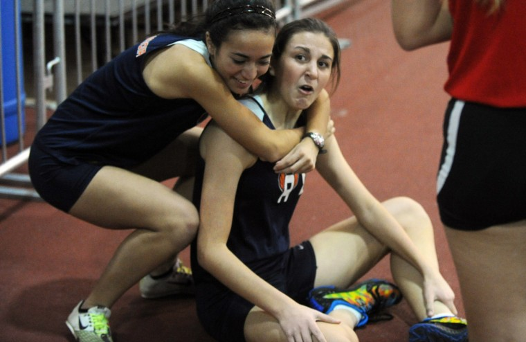 Reservoir's Katie Wilson, left, hugs teammate and out-of-breath anchor runner Julianne Knoblett after their team won the girls 4x800 meter relay event during the Howard County indoor track championships. (Brian Krista/BSMG)