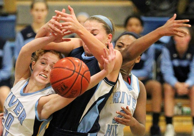 River Hill's Halley Seybold, left, and Sydney Poindexter, right, battle Howard's Sydney Biniak, center, for the ball. (Jen Rynda/BSMG)