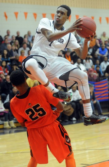 Reservoir's Aaron McDonald jumps over City's Juwan Grant on his way to the hoop during the 3A East regional championship boys basketball game at Reservoir. (Brian Krista/BSMG)