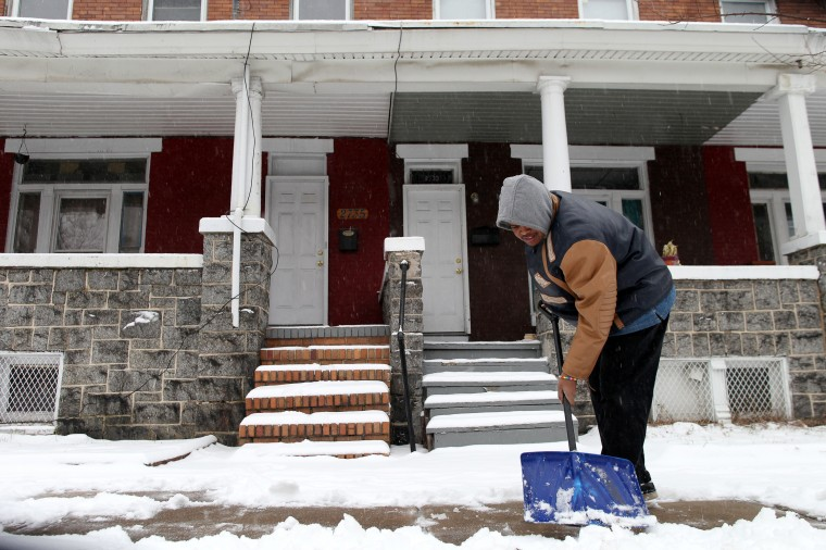 Tevin Pittman shovels the sidewalk in front of his Remington home in Baltimore, MD on Sunday, December 8, 2013. (Jen Rynda/Baltimore Sun)