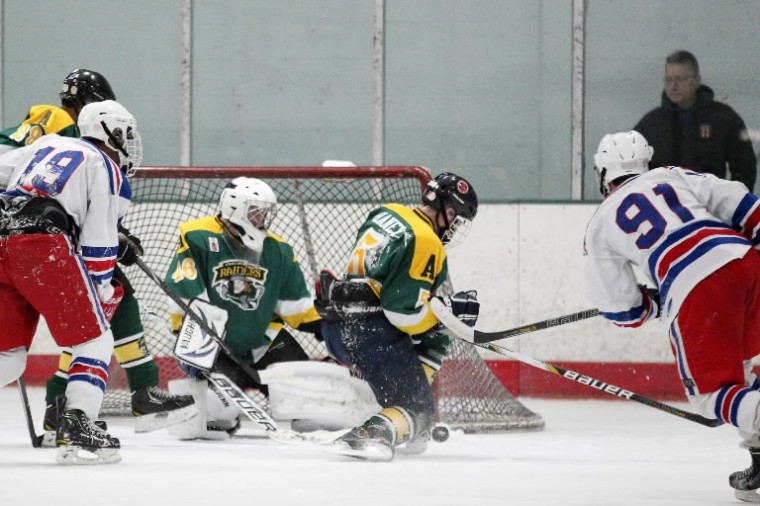 Atholton's Matt Haney, center, blocks a shot by Wootton's Brandon Hall, right, during the ice hockey state semifinal at The Gardens Ice House. (Photo by Jen Rynda/BSMG)