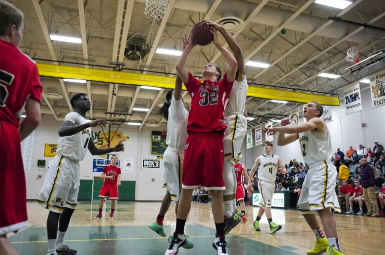 Glenelg's Daine Van de Wall gets his shot blocked by Wilde Lake's Khari Jackson, left, and Antony Evany, right, on Friday, Feb. 28 at Wilde Lake High School.(Photo by Noah Scialom/BSMG)