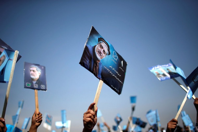 Supporters of Afghan presidential candidate Abdullah Abdullah hold posters of him during an election rally in Parwan province, northern Afghanistan March 20, 2014. Afghanistan's presidential election will be held on April 5, 2014. (REUTERS/Ahmad Masood)