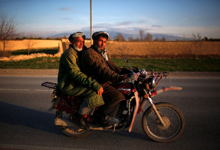 Afghan men dressed in traditional northern cloaks ride on a motorcycle in Mazar-I-Shariff, northern Afghanistan March 27, 2014. (Ahmad Masood/Reuters)