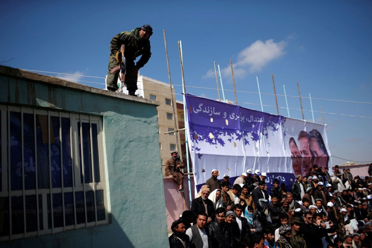 A member of the security personnel keeps watch during a rally by Afghan presidential candidate Zalmai Rassoul in Mazar-I-Shariff, northern Afghanistan, March 27, 2014. The Afghan presidential elections will be held on April 5. (Ahmad Masood/Reuters)