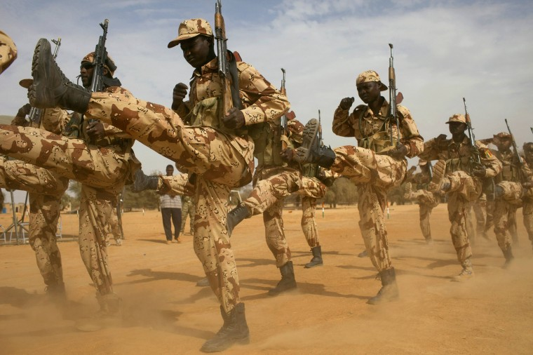 """Chadian soldiers march during Flintlock 2014, a U.S.-led international training mission for African militaries, in Diffa, March 3, 2014. On a dusty training ground in Niger, U.S. Special Forces teach local troops to deal with suspects who resist arrest. The drill in the border town of Diffa is part of Operation Flintlock, a counter-terrorism exercise for nations on the Sahara's southern flanks that the United States organises each year. Washington's aim is to tackle Islamist militants in the Sahel region while keeping its military presence in Africa light. A growing number of European nations taking part shows their increasing concern about security in West Africa. Central to the international effort is a blossoming relationship between the United States and France, the former colonial power and traditional """"policeman"""" of the turbulent region. (REUTERS/Joe Penney)"""