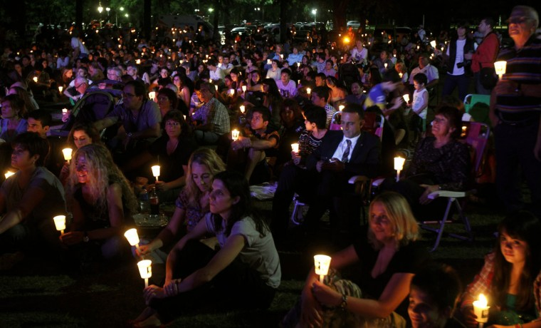 A man looks at his mobile phone as people hold candles outside the Galileo Galilei planetarium to observe Earth Hour in Buenos Aires on March 29, 2014. (REUTERS/Marcos Brindicci)