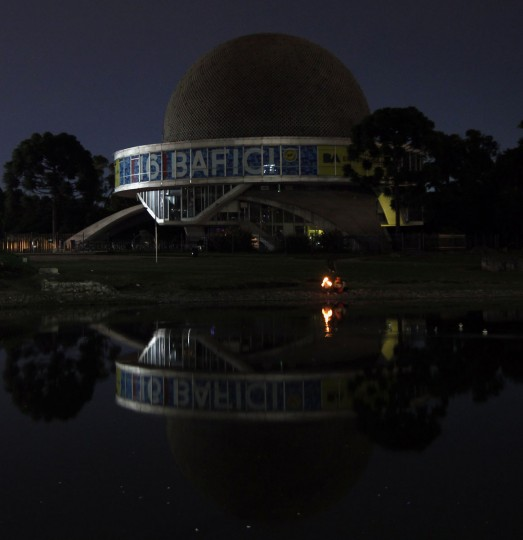 People hold candles as they stand next to a pond in front of the Galileo Galilei planetarium during Earth Hour in Buenos Aires on March 29, 2014. (REUTERS/Marcos Brindicci)