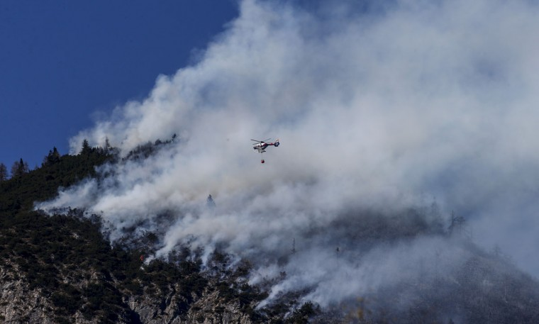 A police helicopter drops water on a forest fire on Runstboden mountain in the western Austrian village of Absam March 20, 2014. Police and fire fighters have been battling the fire since it broke on Thursday police reported. The cause the the blaze is still unknown. (REUTERS/Dominic Ebenbichler)