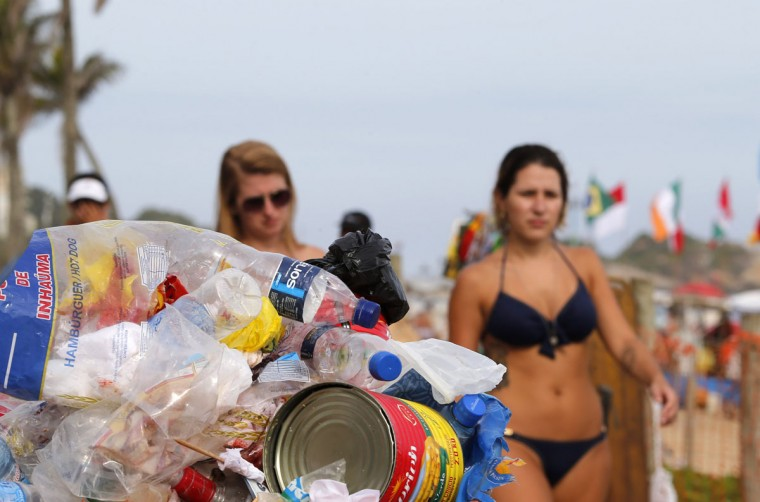Residents walk near a dustbin filled with garbage on Ipanema beach in Rio de Janeiro on March 5, 2014. (REUTERS/Sergio Moraes)