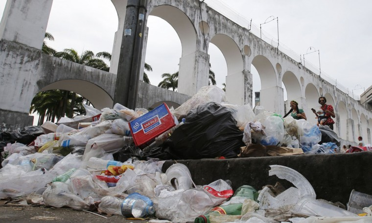 Revellers walk through garbage strewn on a pavement in front of the Arcos da Lapa water duct in Rio de Janeiro on March 5, 2014. (REUTERS/Sergio Moraes)