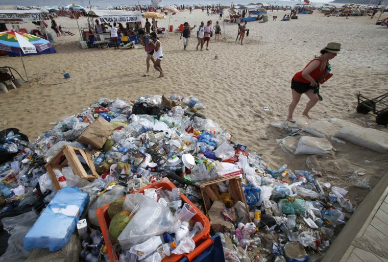 A woman walks past garbage strewn on Ipanema beach in Rio de Janeiro on March 5, 2014. (REUTERS/Sergio Moraes)