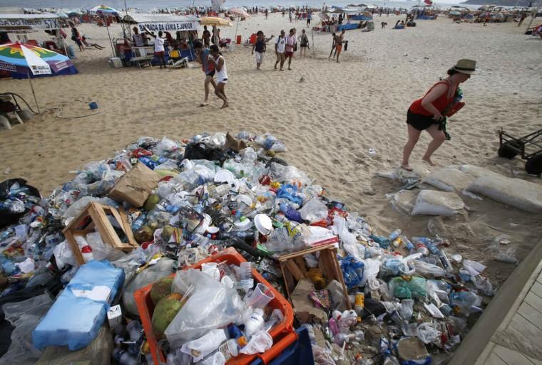 A woman walks past garbage strewn on Ipanema beach in Rio de Janeiro on March 5, 2014. (REUTERS/Sergio Moraes)