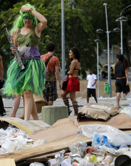 A reveller walks through garbage strewn on the pavement in the Lapa neighborhood in Rio de Janeiro on March 5, 2014. (REUTERS/Sergio Moraes)