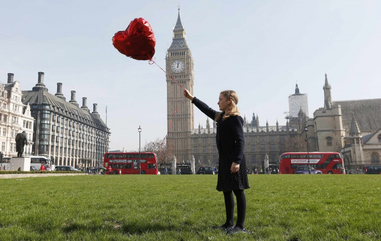 "Mili Baxter poses with a red balloon while recreating the image from artist Banksy's ""There Is Always Hope"" graffiti, on Parliament Square in London March 13, 2014. The release of red balloons took place simultaneously in New York, Washington DC, Moscow, Paris and Zaatari Camp, the largest Syrian refugee camp in Jordan, in an effort to raise awareness on the third anniversary of the Syrian conflict. (REUTERS/Suzanne Plunkett)"