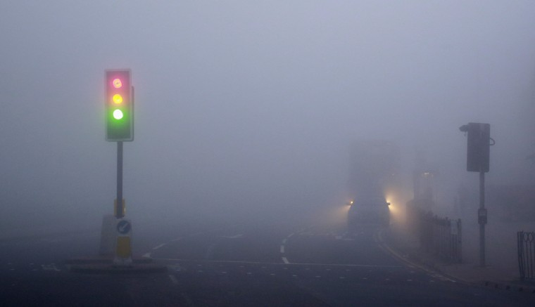 Traffic lights are seen in early morning thick fog in London March 13, 2014. Flights have been cancelled at London City airport and Heathrow, The Woolwich ferry cancelled and low visibility has caused slow traffic on motorways. (REUTERS/Russell Boyce)