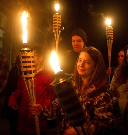 Students and visitors hold torches as they observe Earth Hour outside Fleming College's Frost Campus for Environmental Studies in Lindsay, Ontario on March 29, 2014. (REUTERS/Fred Thornhill)