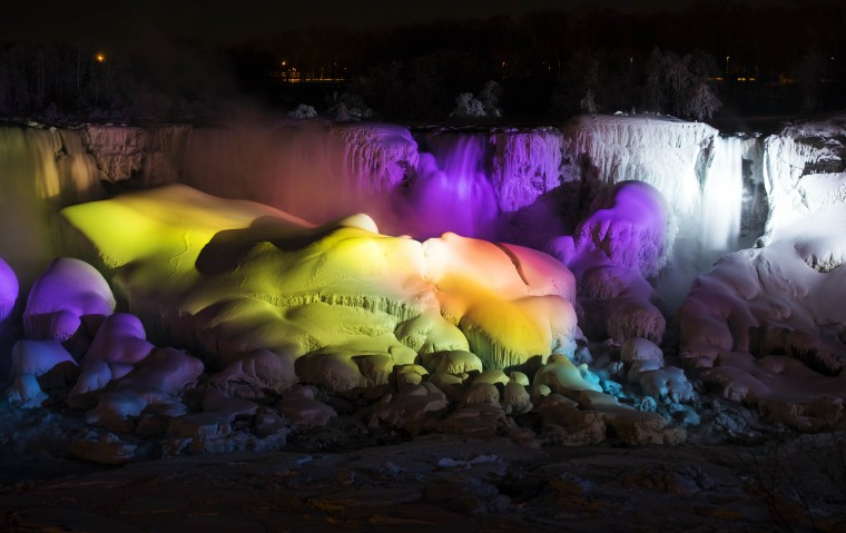 A partially frozen Niagara Falls is seen on the American side lit by lights during sub freezing temperatures in Niagara Falls, Ontario March 3, 2014. (REUTERS/Mark Blinch)