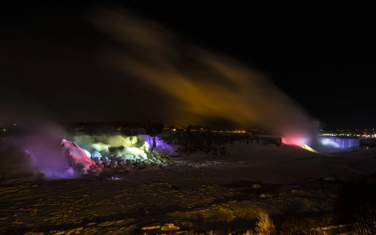 The American Falls and the Horseshoe Falls (R) are seen partially frozen lit by lights during sub freezing temperatures in Niagara Falls, Ontario March 3, 2014. (REUTERS/Mark Blinch)