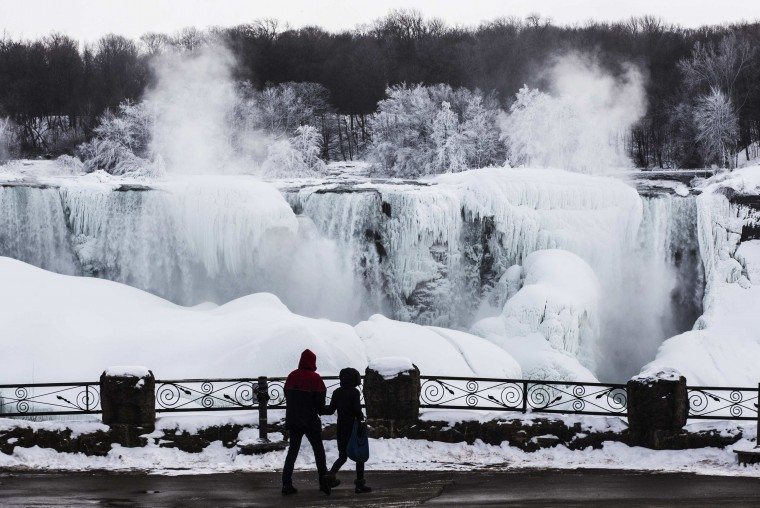 A couple looks out over the partially frozen American side of the Niagara Falls during sub-freezing temperatures in Niagara Falls, Ontario March 3, 2014. (REUTERS/Mark Blinch)