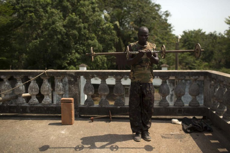 A former soldier of the Armed Forces of the Central African Republic (FACA) lifts weights in the crumbling former palace of the late self-proclaimed Emperor Jean-Bedel Bokassa near the village of Barengo, south of the capital Bangui March 17.  || PHOTO CREDIT: SIEGFRIED MODOLA  - REUTERS