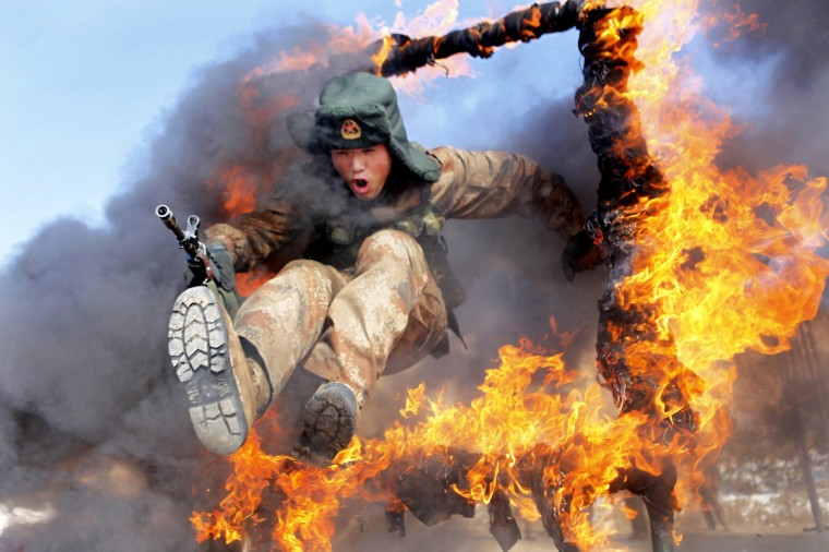 A frontier soldier from the People's Liberation Army jumps through a ring of fire as part of training in Heihe, Heilongjiang province. (China Daily)