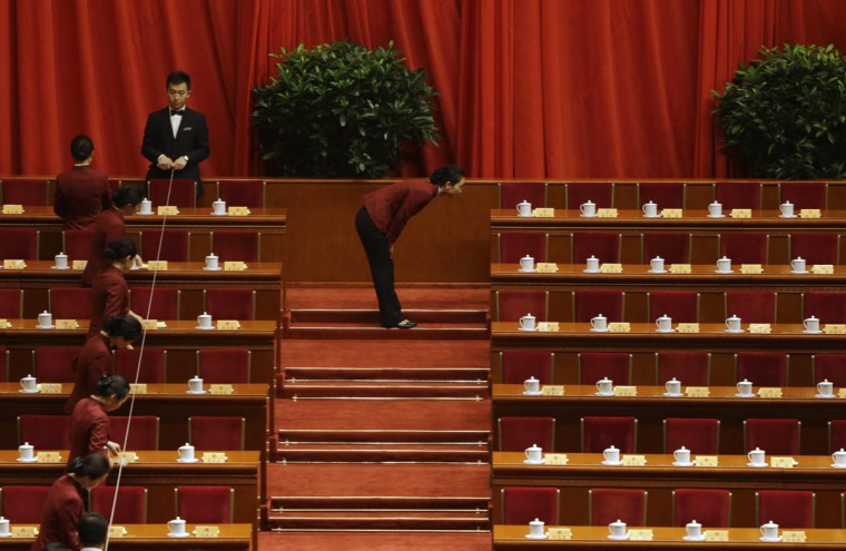 Attendants adjust tea cups before the opening ceremony of Chinese People's Political Consultative Conference (CPPCC) at the Great Hall of the People in Beijing, March 3, 2014. (Jason Lee/Reuters)