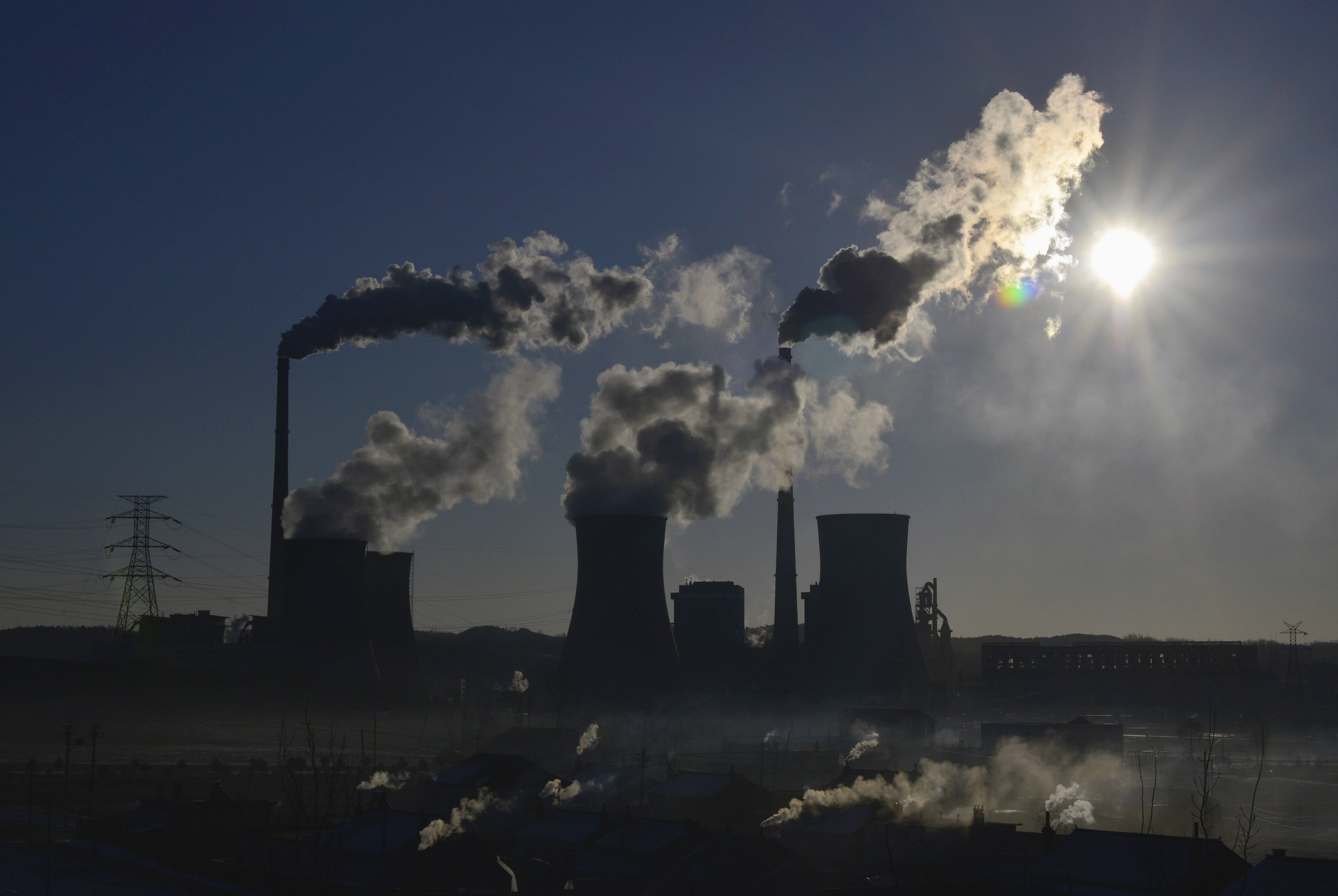 Smoke rises from chimneys and cooling towers of a thermal power