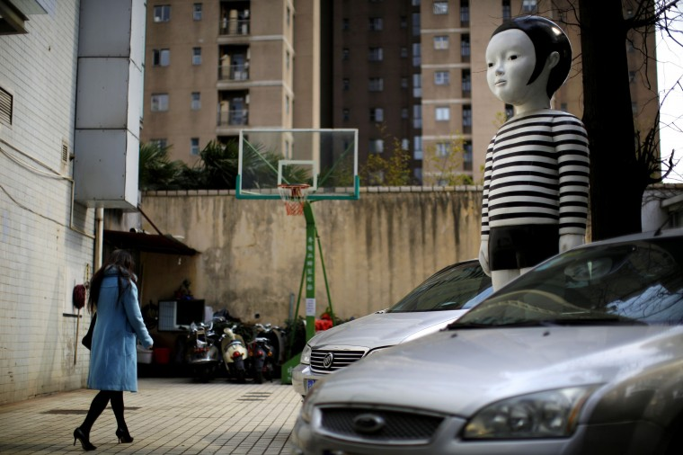 A giant doll boy is seen at an apartment parking area in downtown Shanghai March 7. CREDIT: CARLOS BARRIA - REUTERS