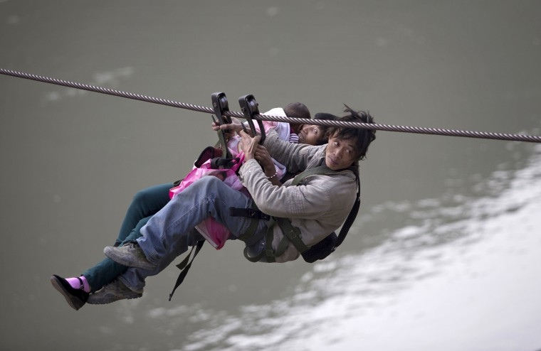 A man, his wife and their child use a zip-line to cross the Nujiang River in Lazimi village of Nujiang Lisu Autonomous Prefecture. Residents have been using the zip-line for years to cross the river as there is no bridge nearby, local media reported. (Wong Campion/Reuters)