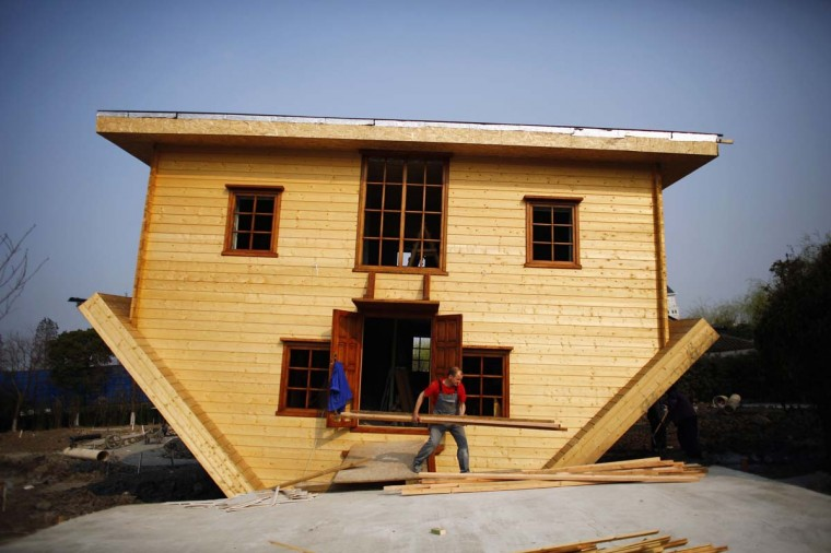 """A labourer works at an upside-down house under construction at Fengjing Ancient Town, Jinshan District, south of Shanghai, March 17. Workers are putting the final touches on this eccentric tourist attraction built at the """"China Folk Painting Village"""". Furniture will also be placed upside down in the house, which is expected to open the public in April, according to local media.   