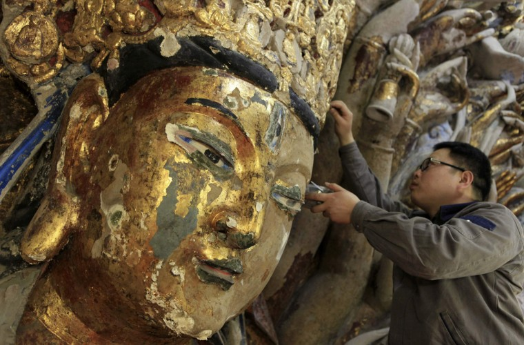 A restoration worker peels off loose gold foil as part of a restoration project for an 800-year-old Thousand-Hand Guanyin Buddhist statue on Mount Baoding in Chongqing municipality, March 18, 2014. The stone-carving statue, which takes up about 88 square metres on the mountain, dates back to the Southern Song Dynasty (1127-1279). Officials said the restoration project started in April 18, 2011 and would likely finish in the first half of 2015, local media reported. (Stringer/Reuters)