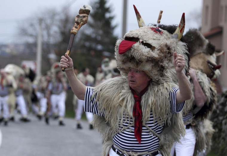 """Bell ringers, or """"Zvoncari"""", take part in a parade in a village near Rijeka, Crotia on March 2, 2014. According to traditional customs, the bell ringers would walk through different villages and create huge amounts of noise to scare away evil spirits of winter and welcome spring. Their costumes consist of white trousers and striped shirts, including a sheepskin thrown over their shoulders and a big bell tied around their waist. (Antonio Bronic/Reuters)"""
