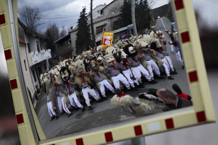 """Bell ringers, or """"Zvoncari"""", are reflected in a mirror during a parade in a village near Rijeka, Croatia on March 2, 2014. According to traditional customs, the bell ringers would walk through different villages and create huge amounts of noise to scare away evil spirits of winter and welcome spring. Their costumes consist of white trousers and striped shirts, including a sheepskin thrown over their shoulders and a big bell tied around their waist. (Antonio Bronic/Reuters)"""