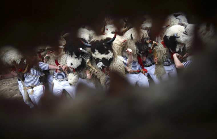 "Bell ringers, or ""Zvoncari"", are seen through a mask during a parade in the village of Marcelji, Croatia, March 2, 2014. (Antonio Bronic/Reuters)"